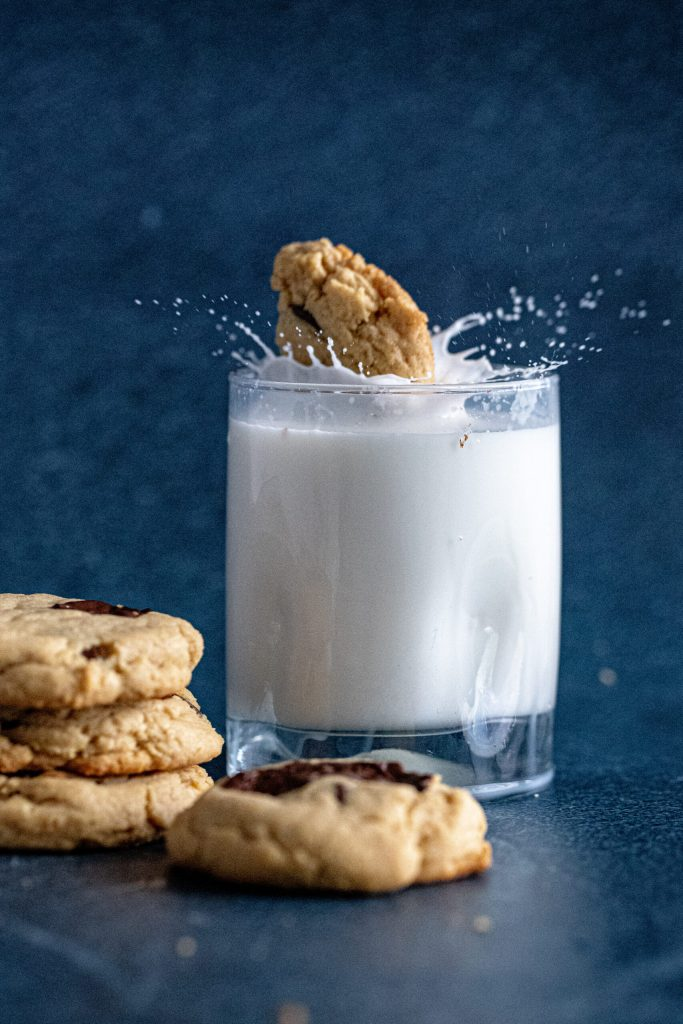 peanut butter chocolate chunk cookie being dropped into a glass of milk