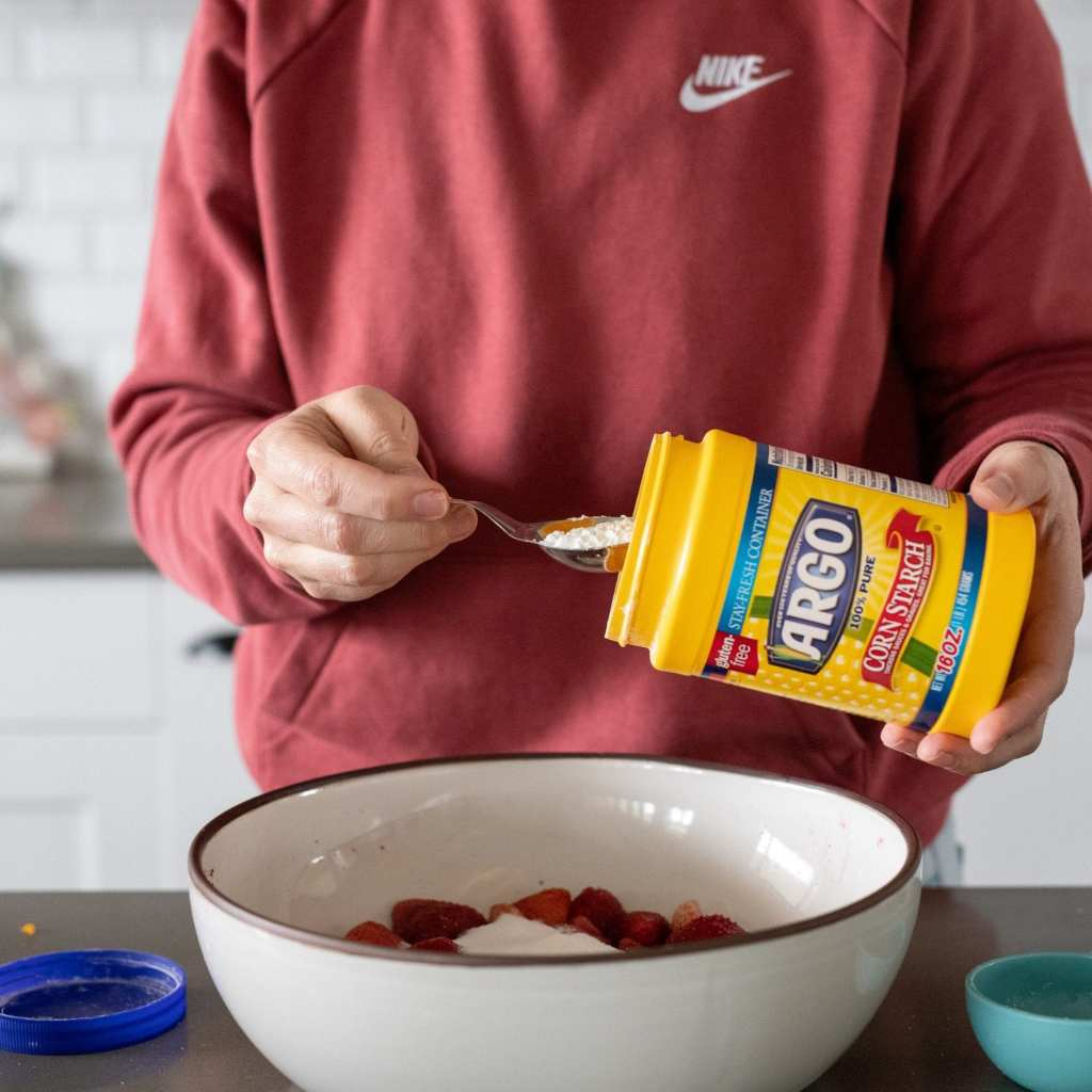 pouring cornstarch onto sugar and strawberries in large bowl.