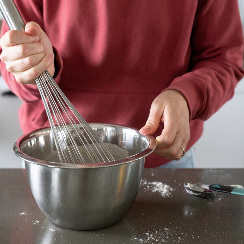 mixing batter with whisk in bowl for cobbler
