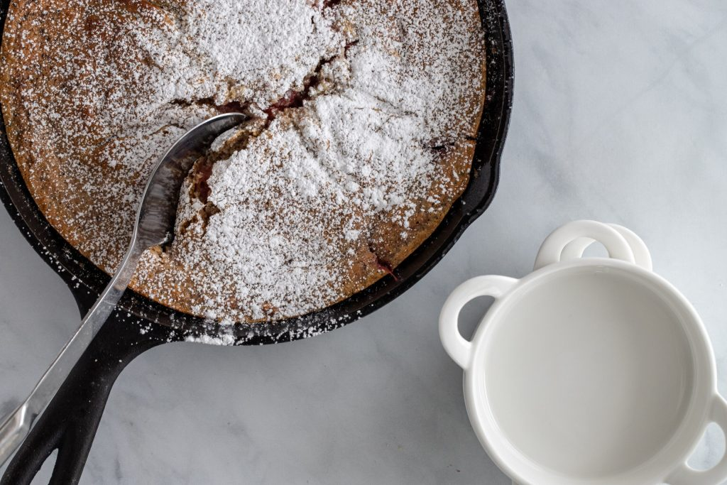 strawberry cobbler in cast iron skillet with serving spoon in it.