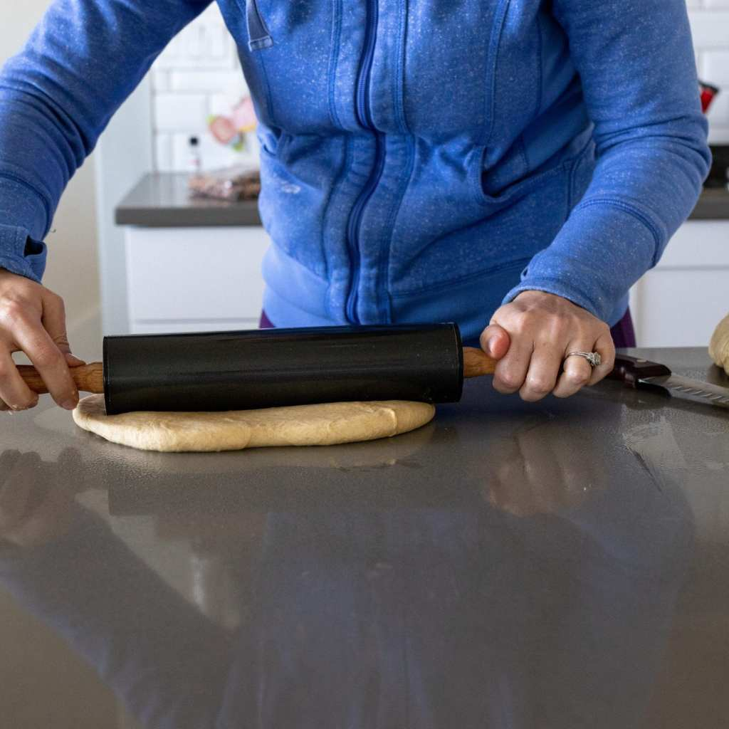 woman rolling bread dough into a rectangle with a rolling pin on a surface