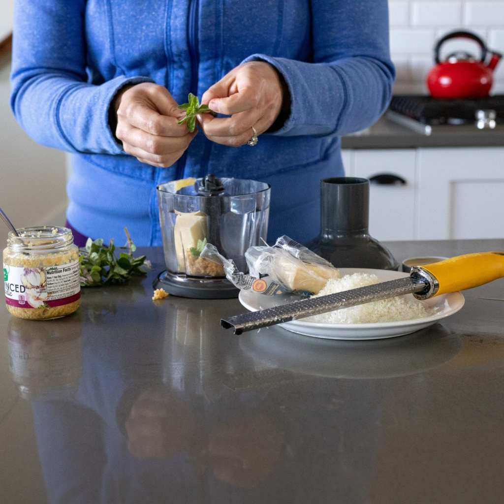 woman adding herbs to a small food processor with grated parmesan and minced garlic.