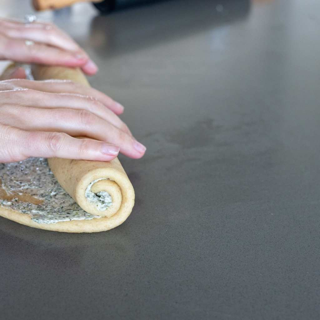 woman rolling swirled herb bread on surface