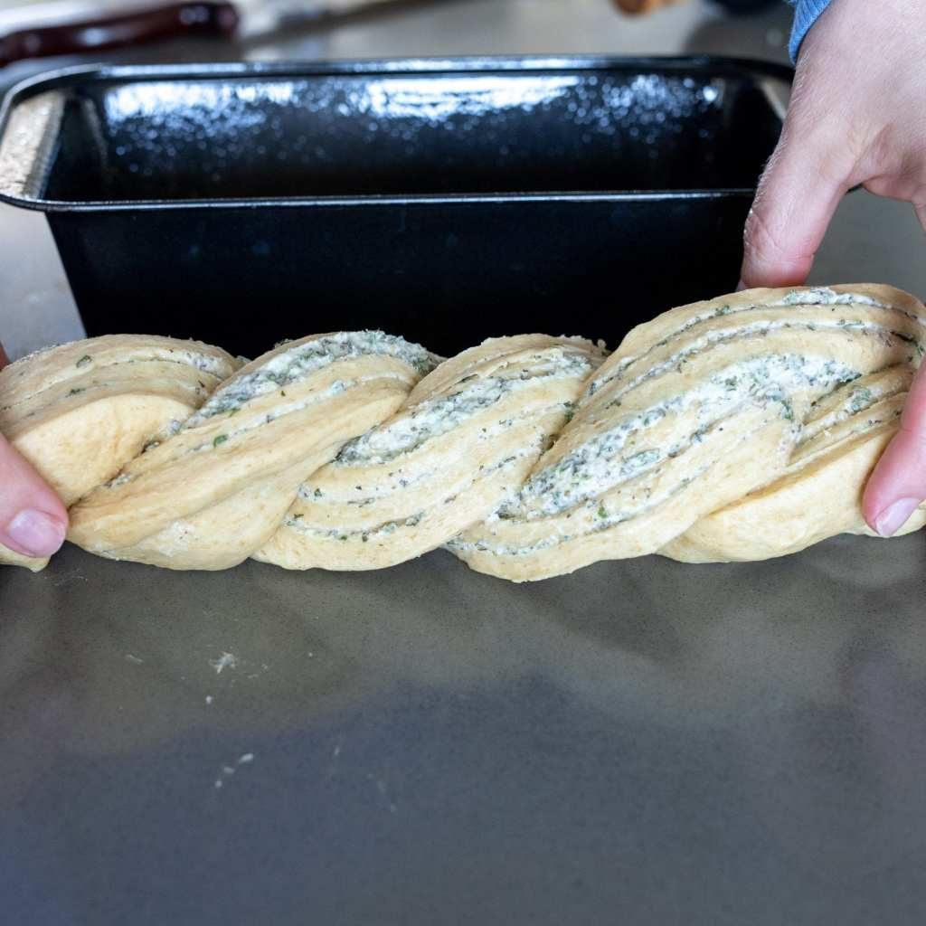 twisted herb bread loaf on quartz surface