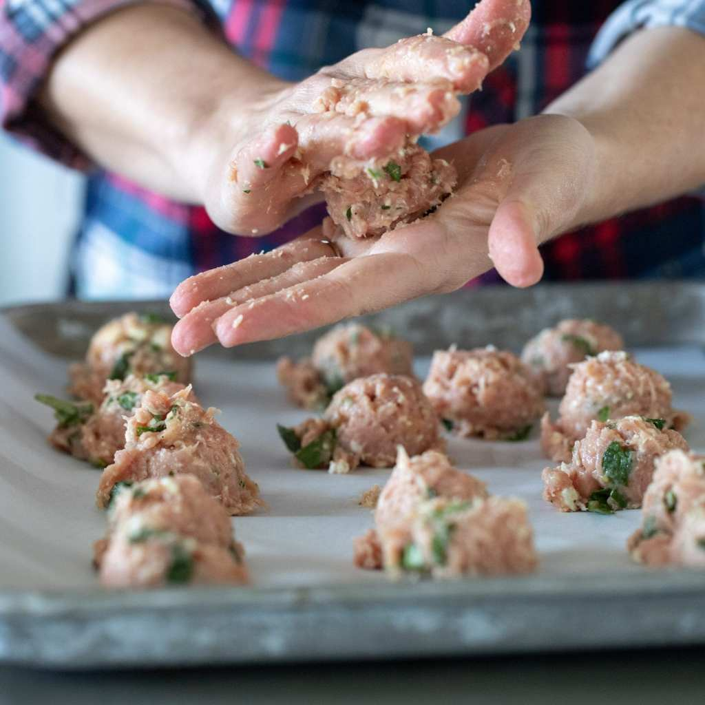 forming turkey meatballs onto parchment lined baking sheet