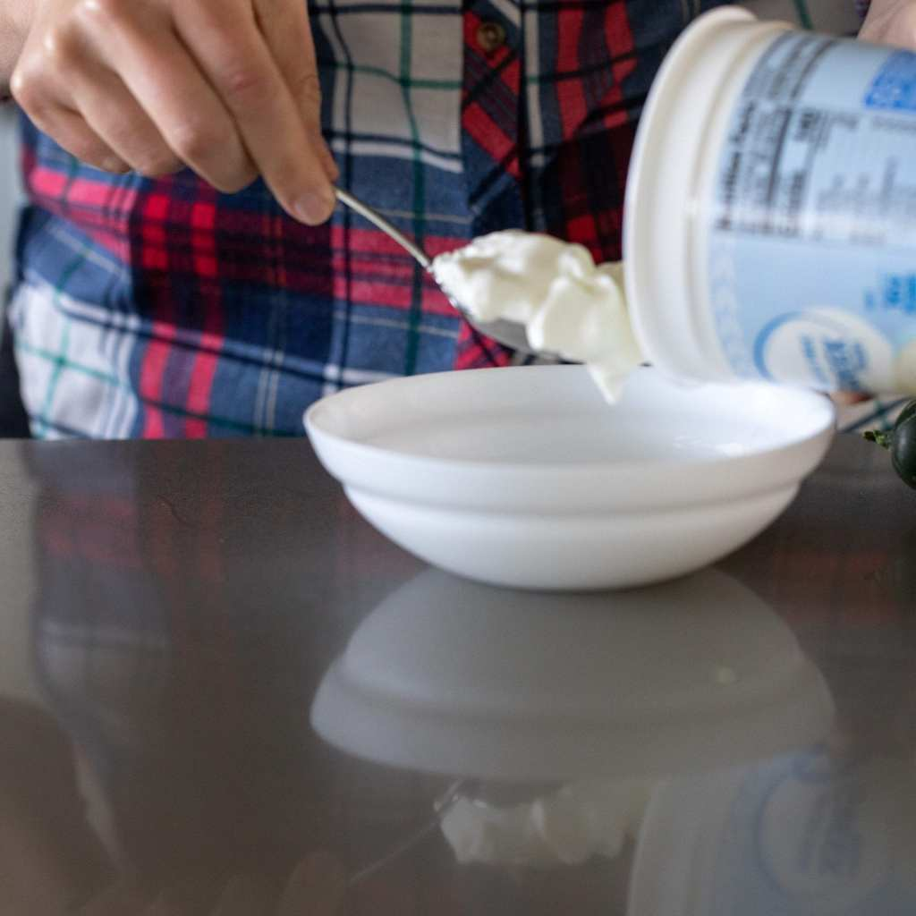 scooping nonfat yogurt into bowl with spoon