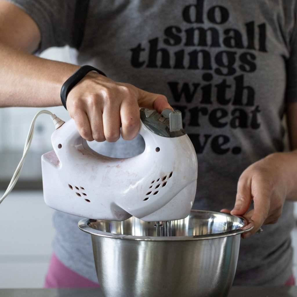 woman mixing eggs and sugar in metal bowl with hand mixer
