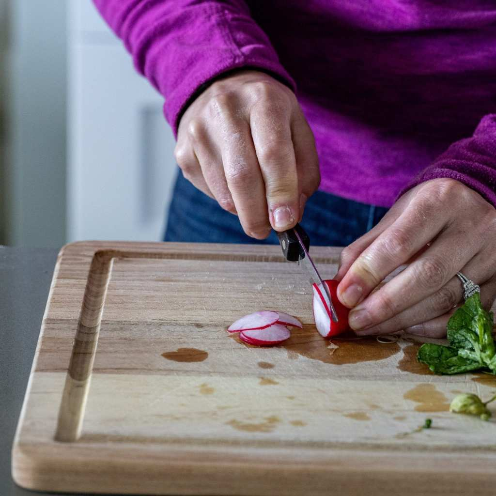 woman slicing radishes on wood cutting board with paring knife.