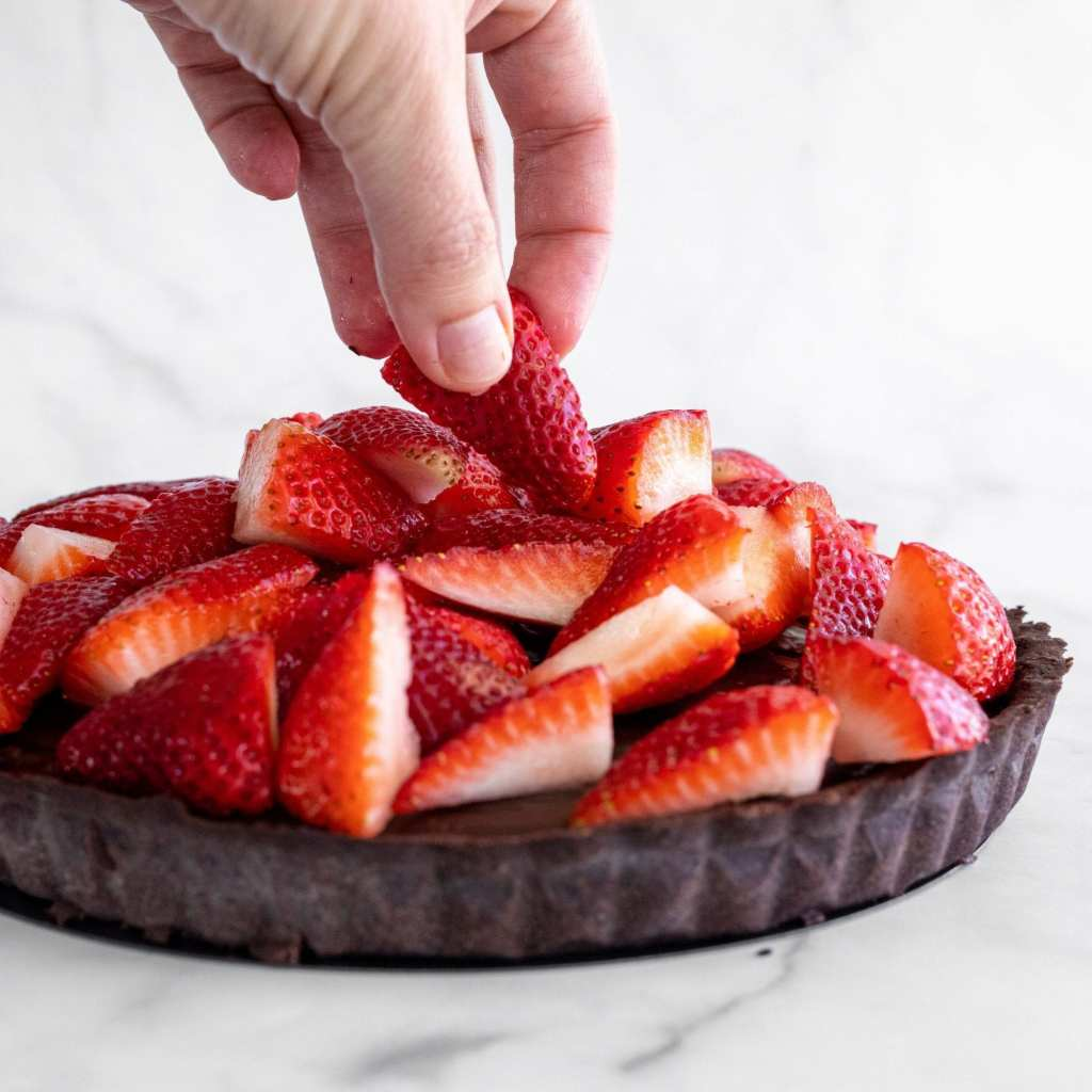 woman adding quartered strawberries on top of chocolate tart