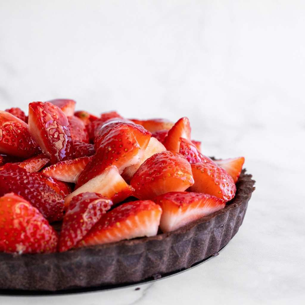 quartered strawberries piled on top of a chocolate ganache tart.