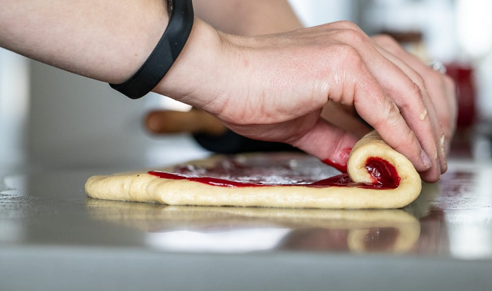 woman rolling raspberry sweet rolls on counter top