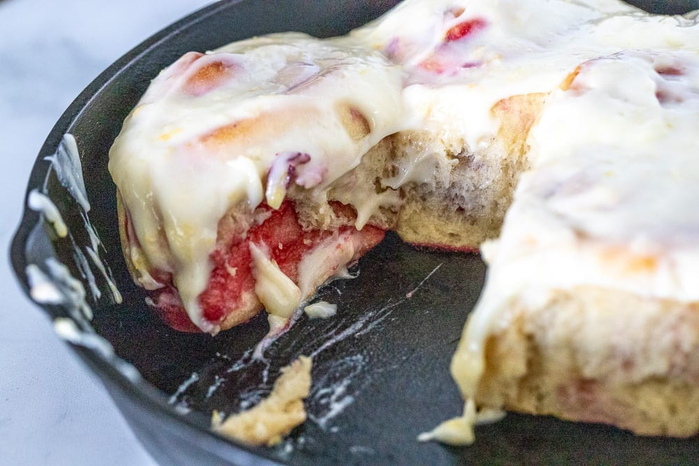 raspberry sweet rolls covered in lemon cream cheese icing in cast iron skillet