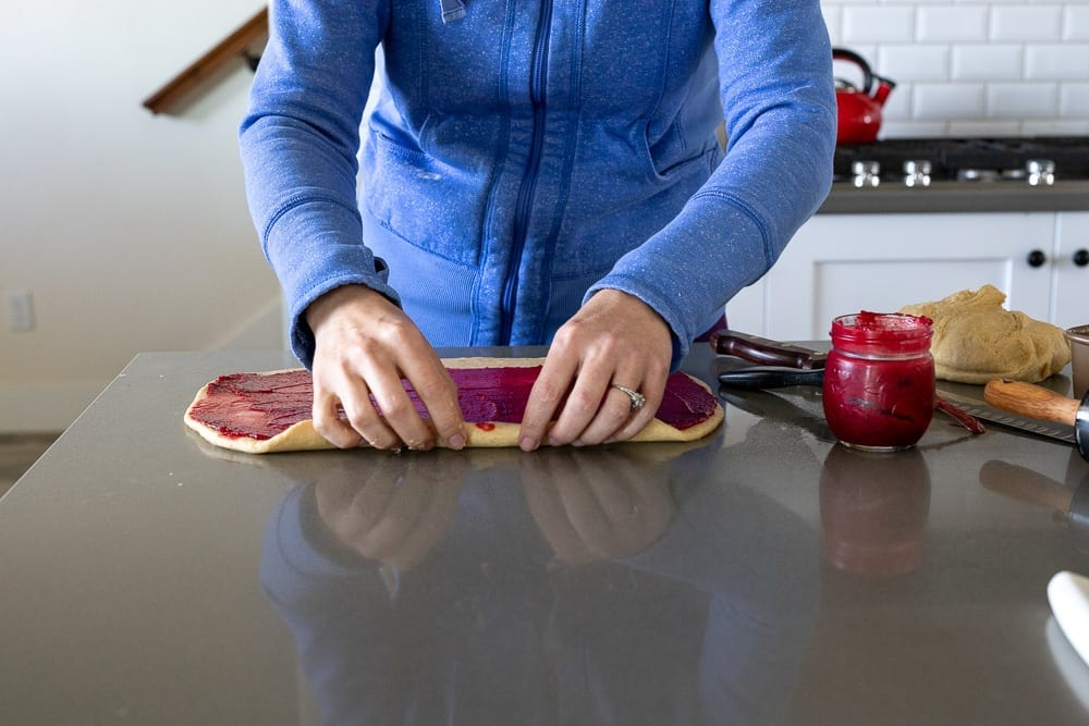 woman rolling whole grain sweet rolls on counter top