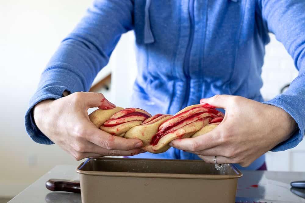 woman placing raspberry swirl loaf into baking pan
