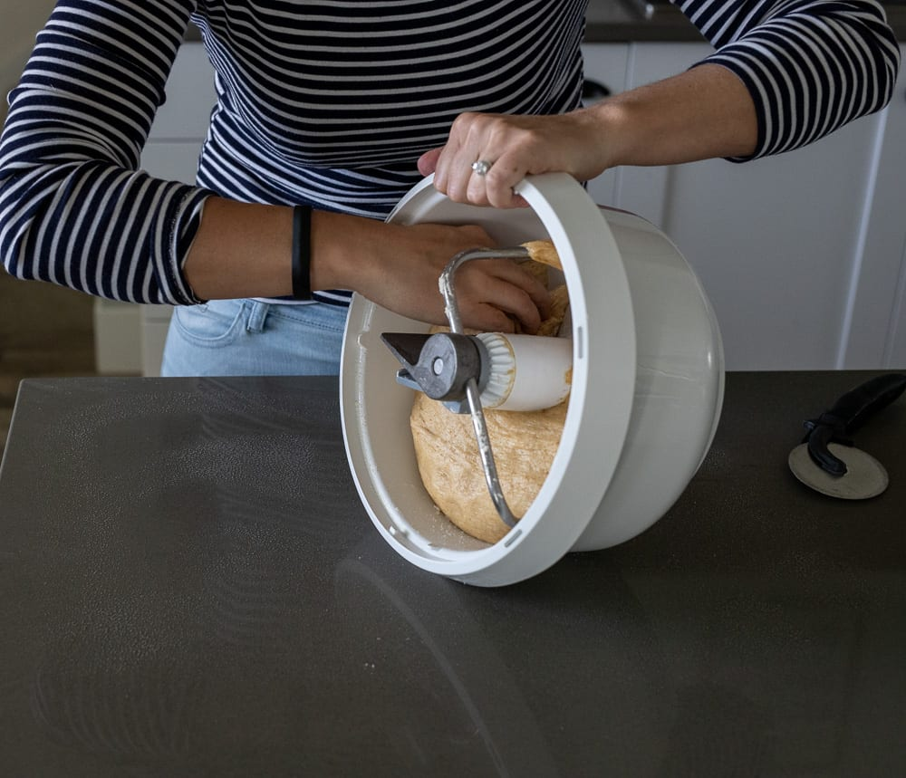 woman removing whole grain sweet dough from bosch mixing bowl