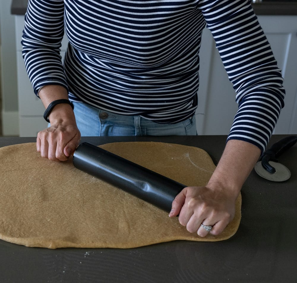 woman rolling out whole grain pie dough on counter top with black rolling pin
