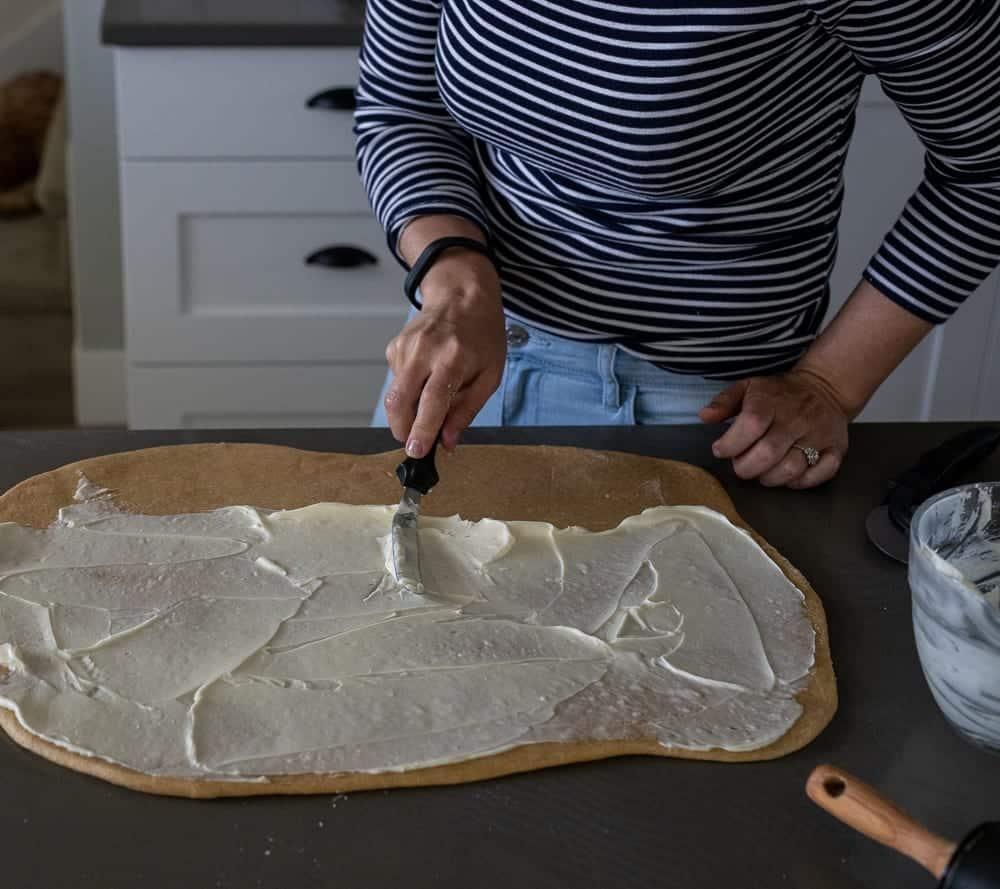 woman spreading sweetened cream cheese mix on whole grain bread dough