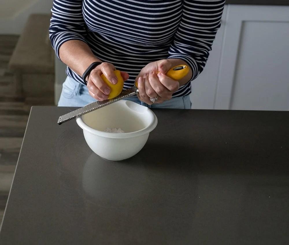 woman zesting a lemon with a microplane zester