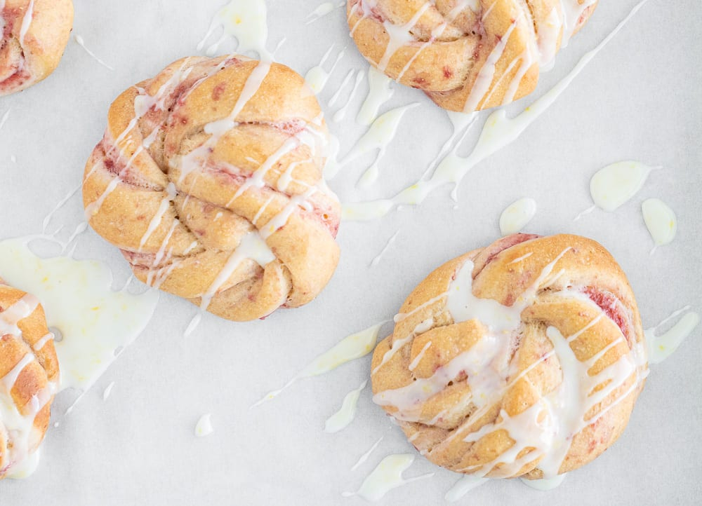 baked strawberry and cream rolls drizzled with cream cheese icing