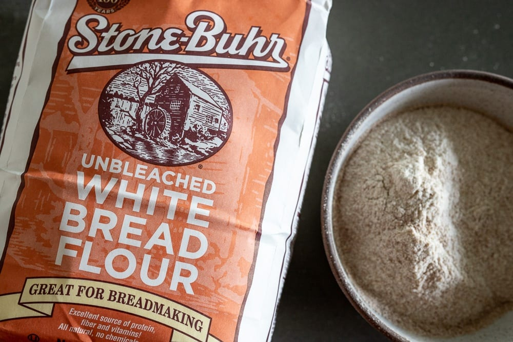 stone buhr bread flour on counter top and ground flour in ceramic bowl