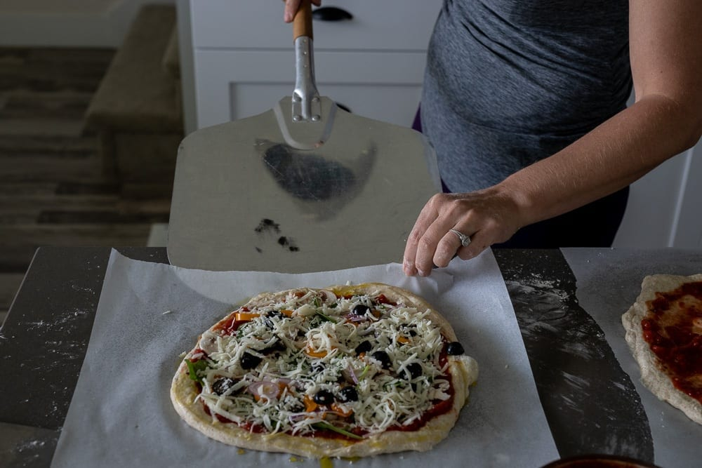 woman using peel to move pizza to oven