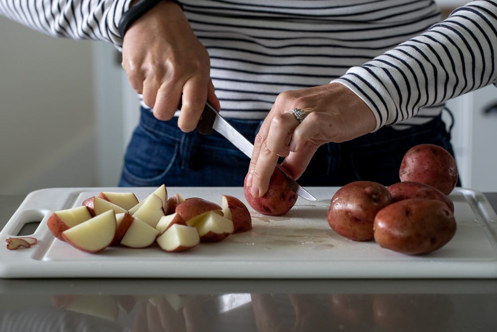 woman chopping red potatoes on white cutting board