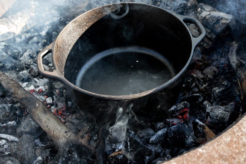 heating up a dutch oven in a bed of coals for cooking a campfire breakfast