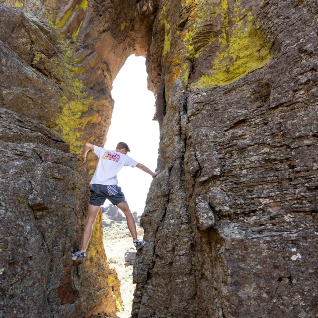 boy climbing on hoodoos in idaho