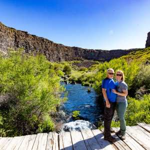 Husband and wife standing on bridge in Box Canyon Springs state park Idaho