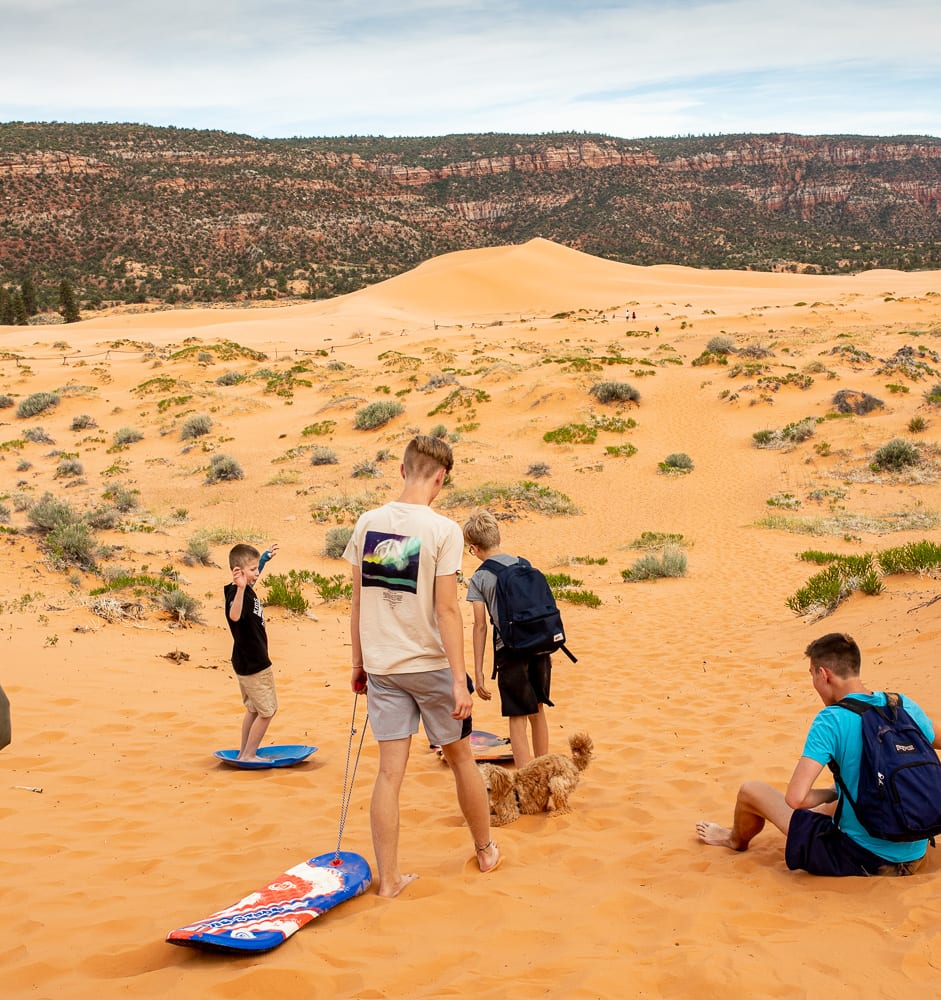 group of boys with sleds walking up to sand dunes. Cavapoo in the background