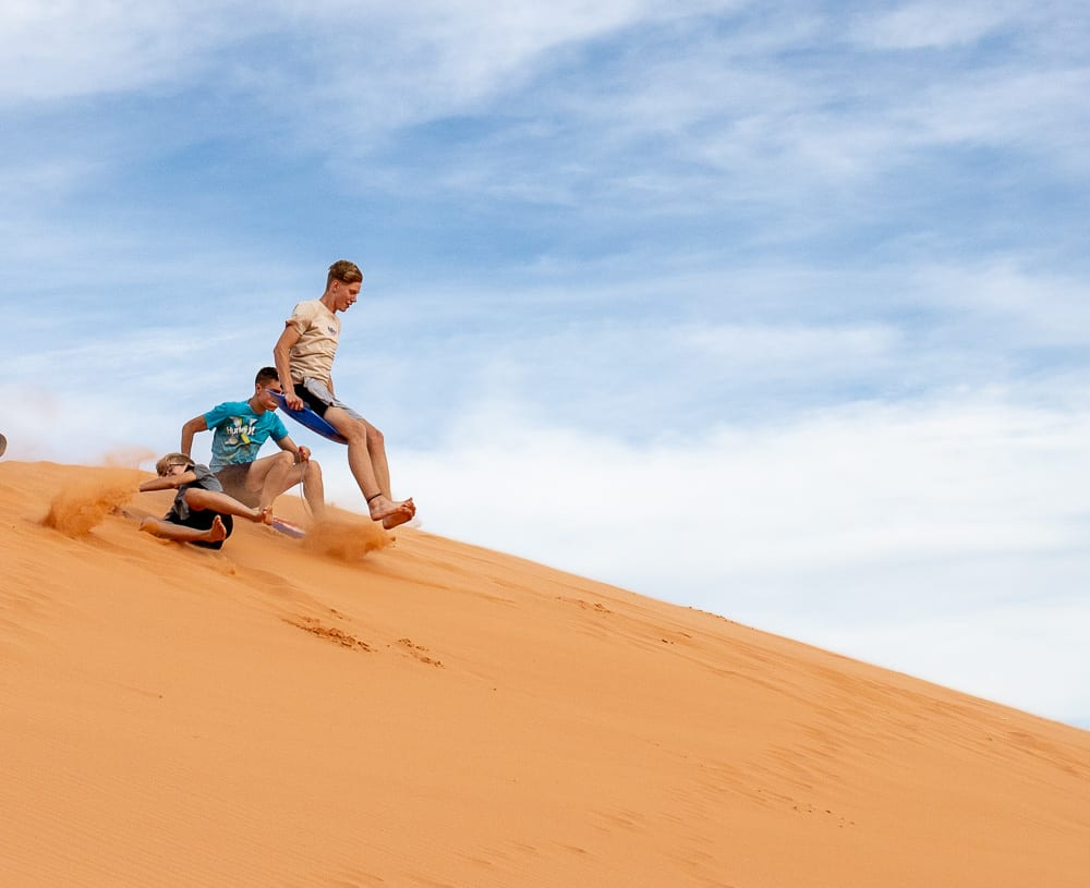 boy in air on sled on coral pink sand dunes. another boy rolling down the dunes
