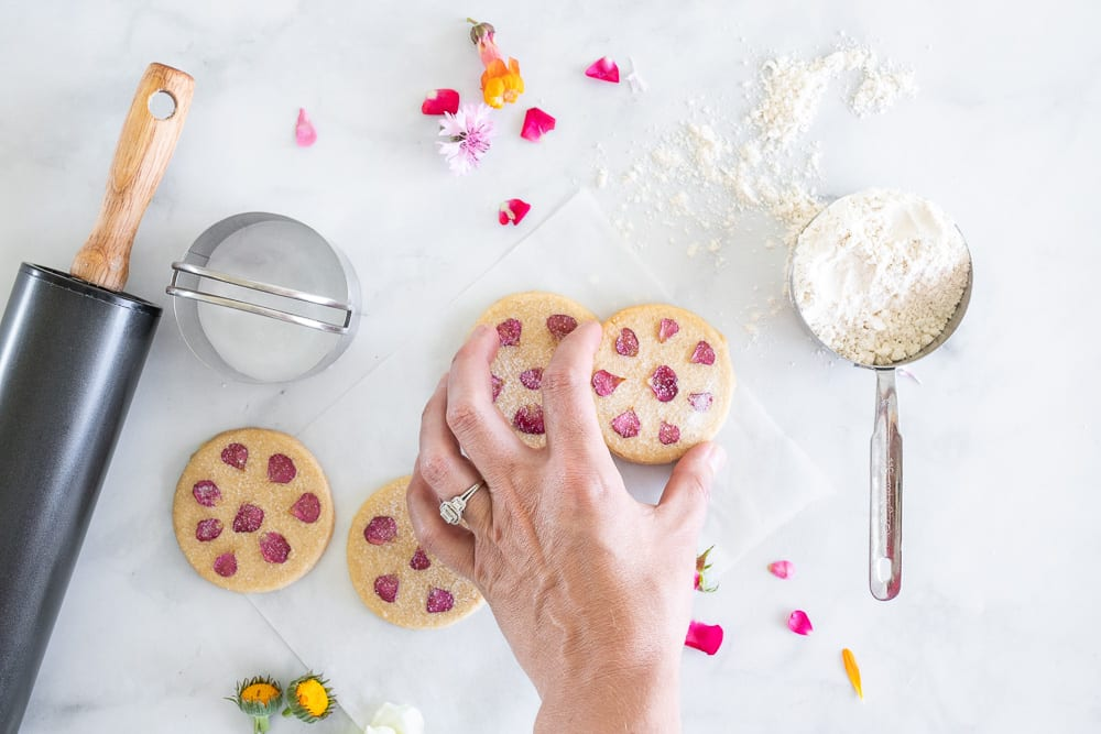 shortbread cookies with edible flowers, rose petals on the counter top. woman picking up one of the cookies. Rolling pin on surface