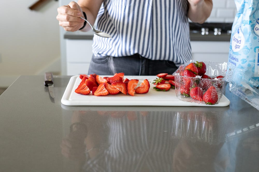 woman sprinkling sugar over strawberries on white plastic cutting board