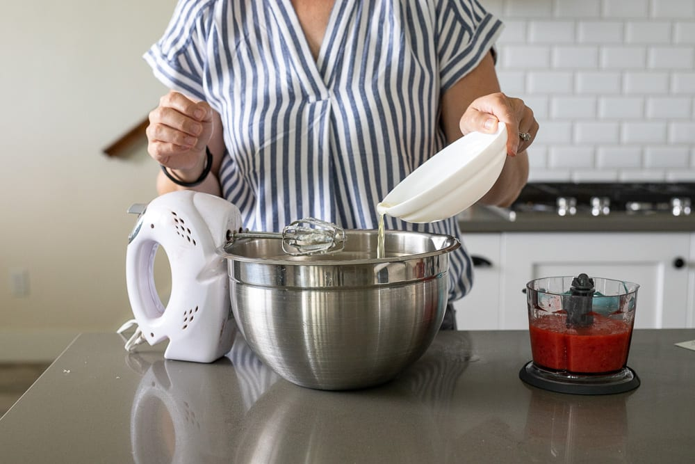 woman pouring egg whites into stainless steel mixing bowl. hand mixer next to bowl and pureed strawberries in small food processor