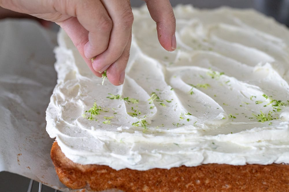woman sprinkling lime zest onto lime buttercream on roasted strawberry cake