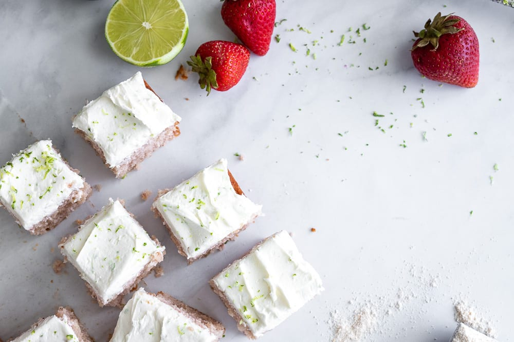 strawberry cake with lime buttercream cut in squares on marble surface with fresh strawberries and limes