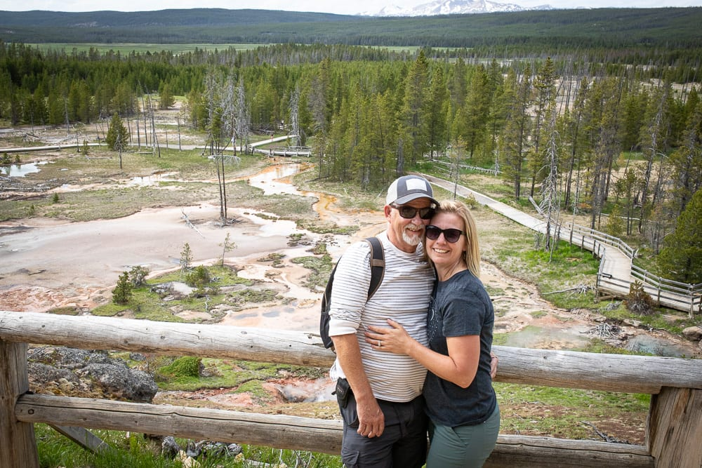 couple sitting in front of hot springs in yellowstone national park