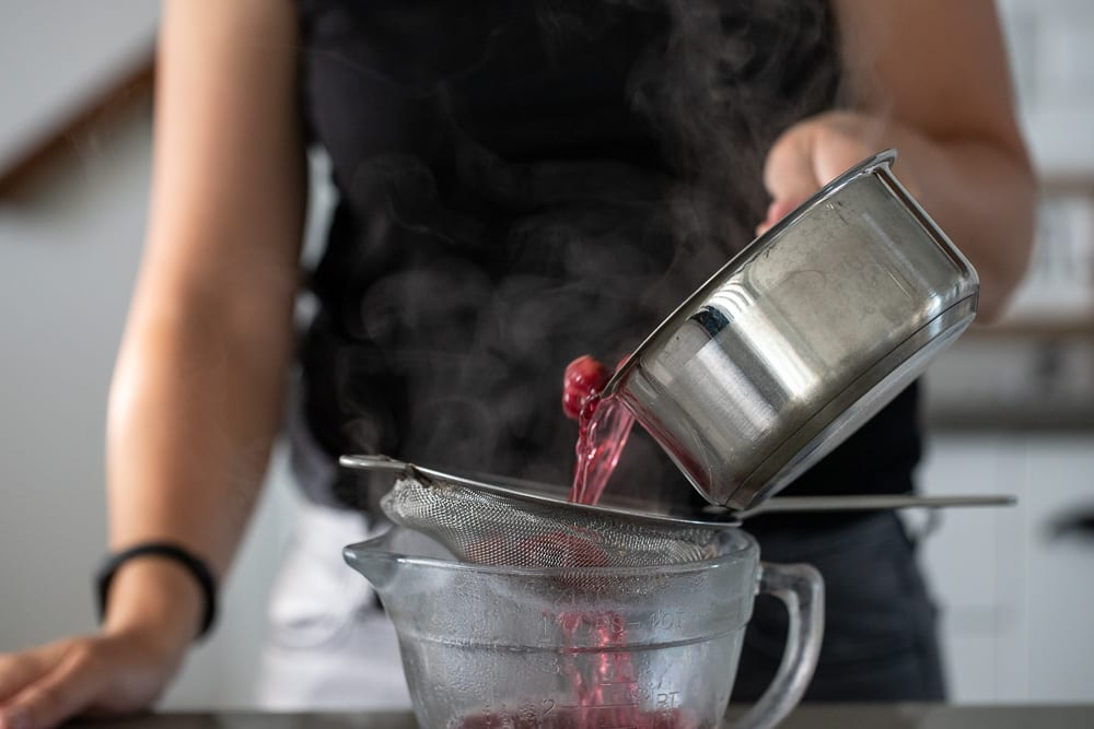 woman straining cherry syrup through fine mesh strainer into a glass 4 cup measuring cup.