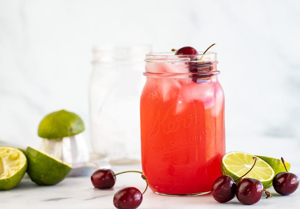 Cherry limeade in mason jar with fresh cherries on top. Lime and cherries on the surface