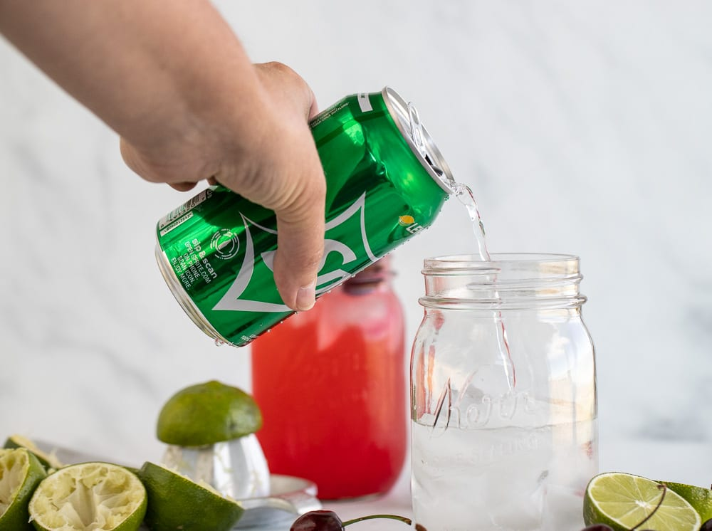 woman pouring 7-up into mason jars. Limes and cherries on the surface