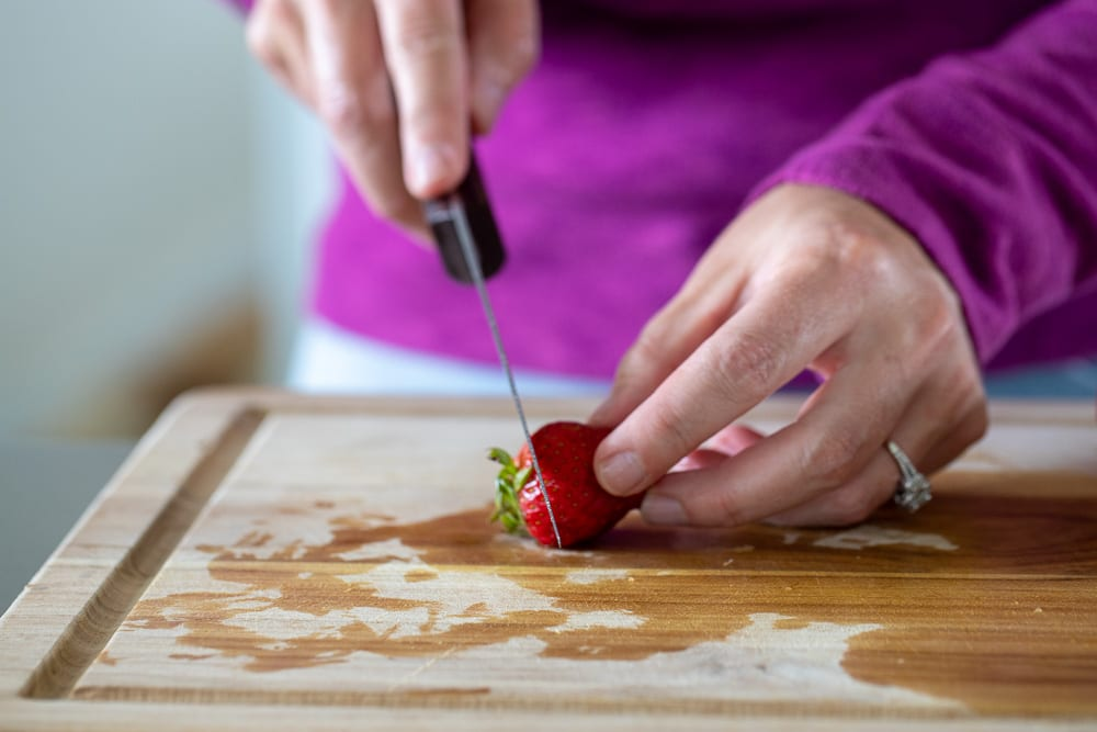 woman cutting off top of strawberry