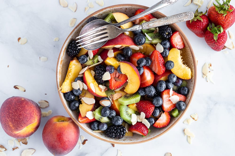 fruit salad in ceramic bowl with peaches and slices almonds and strawberries on surface