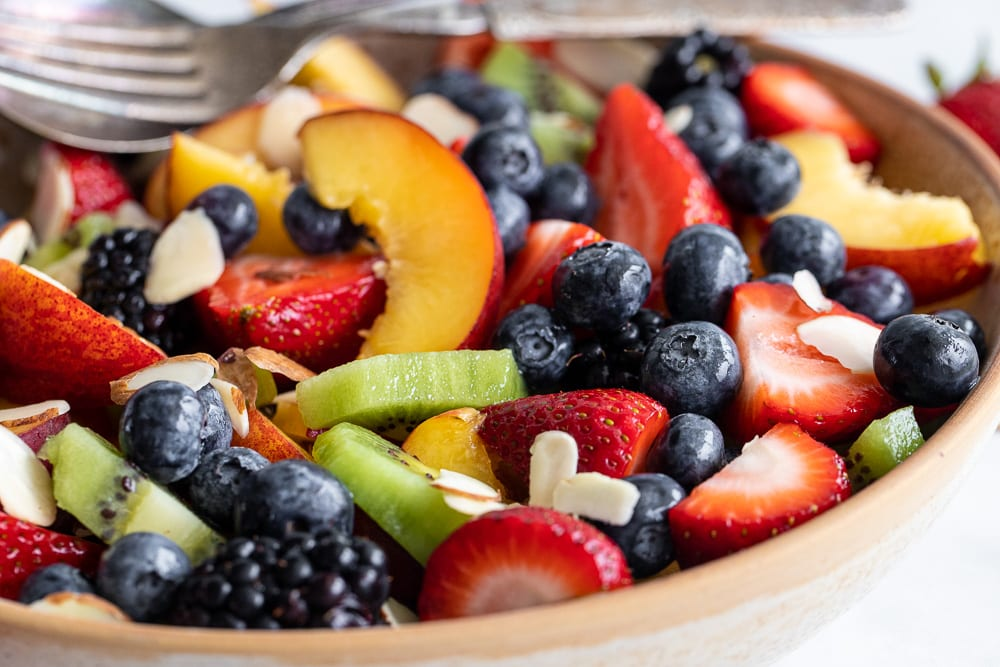fruit salad with honey lime in ceramic bowl