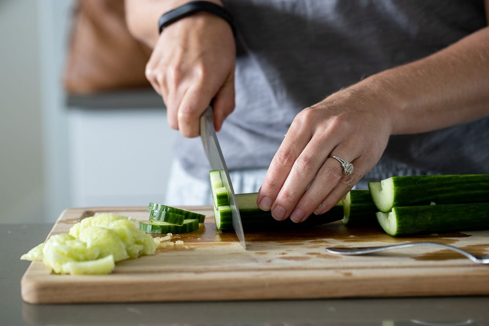 woman cutting seeded cucumbers with a chef's knife preparing for the italian vegetable salad