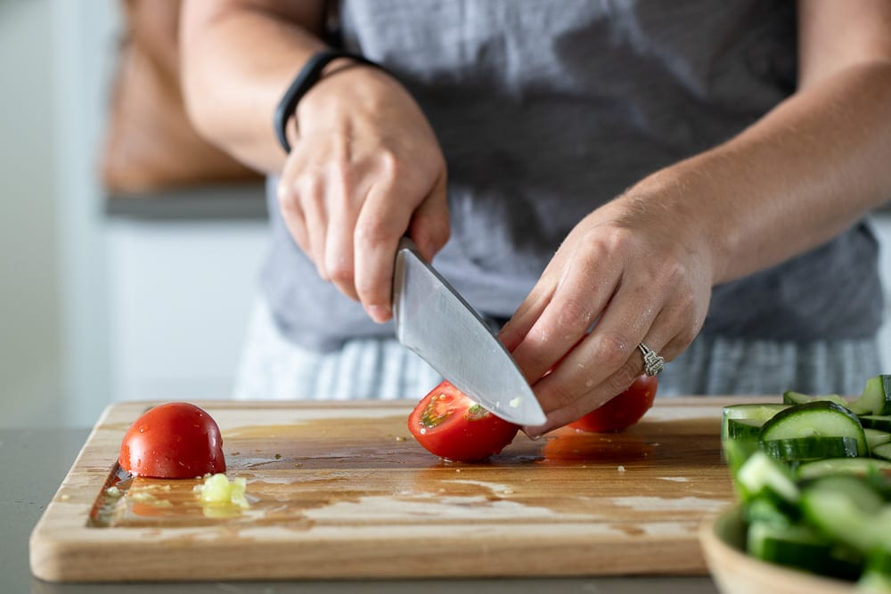 woman cutting red tomatoes on a wood cutting board with chef's knife