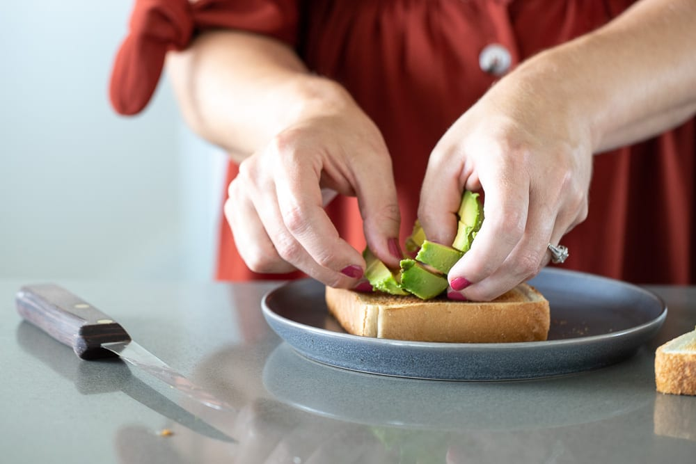 woman putting avocado slices on texas toast for a blat sandwich