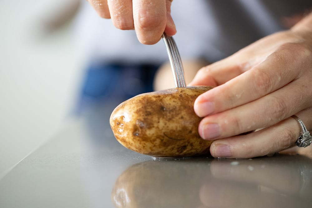 woman poking potato in preparation for baking
