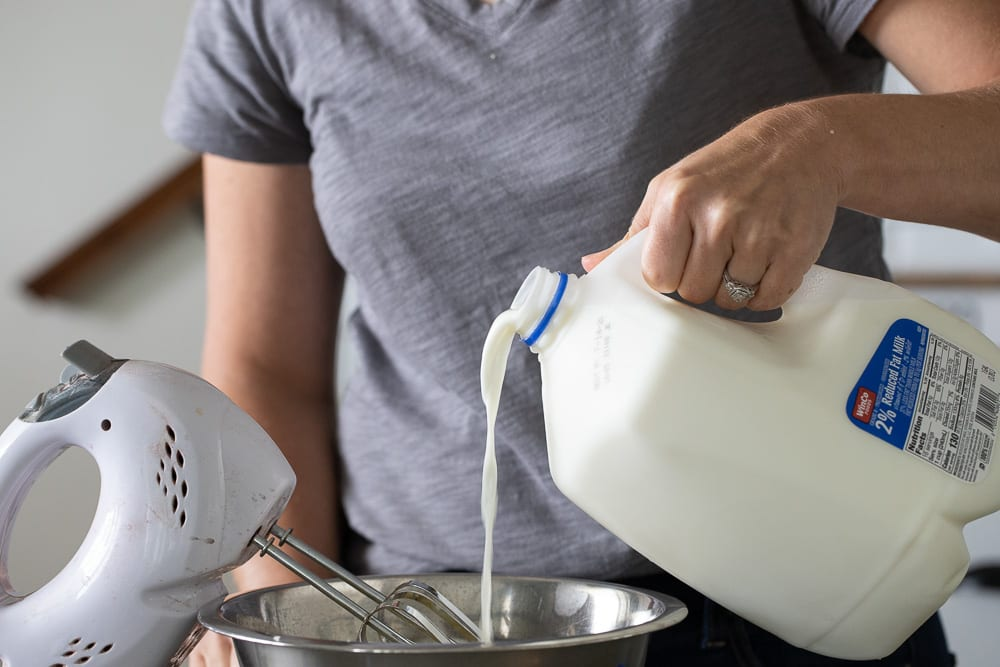 woman pouring milk into a medium sized metal bowl with mixer on the side.