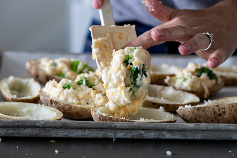 woman spooning filling into twice baked  potatoes with broccoli