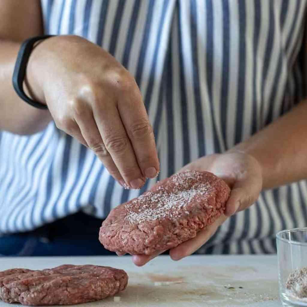 woman sprinkling burger with seasoning